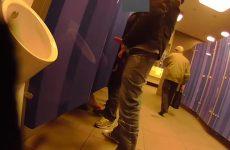 Homo staat te trekken in goed bezocht openbaar toilet