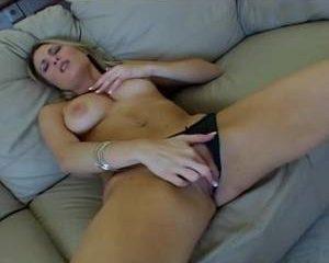 Met alleen haar slipje en hoge hakken aan masturbeert ze