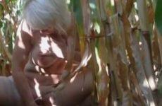 De oude teef mastubeerd met een maiskolf midden in het veld