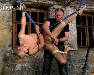 Hangend in touwen wordt hij afgetrokken en anal gamastubeerd