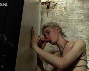 Vastgeketend aan de ketting pijpt de jongen de stijve lul