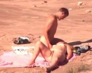 Hij neukt zijn vrouw op het strand niet wetend dat ze gefilmd worden